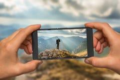 Machen des Fotos des Mannes und der Berge mit Handy Stockbild