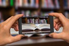 Machen des Fotos des offenen Buches in der Bibliothek mit Handy Lizenzfreie Stockfotos