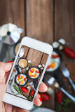 Machen des Lebensmittelfotos des Frühstücks mit Spiegeleiern durch intelligentes Telefon Stockfotografie