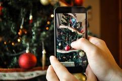 Machen eines Fotos eines Weihnachtsbaums mit einem Smartphone Lizenzfreies Stockbild