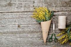 Machen Sie Blumenstrauß von der Mimose Verbände Schnur und Scheren auf rustikalem Holztisch Stockfotografie