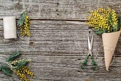 Machen Sie Blumenstrauß von der Mimose Verbände Schnur und Scheren auf rustikalem Holztisch Stockbild