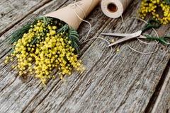 Machen Sie Blumenstrauß von der Mimose Verbände Schnur und Scheren auf rustikalem Holztisch Stockbilder
