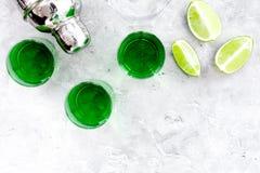 Machen Sie Cocktail mit Wermut Schüttel-Apparat, Schüsse, Kalkscheiben auf grauem Draufsichtraum des Hintergrundes für Text lizenzfreie stockfotos