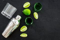 Machen Sie Cocktail mit Wermut Schüttel-Apparat, Schüsse, Kalkscheiben auf schwarzem Draufsichtraum des Hintergrundes für Text stockbilder