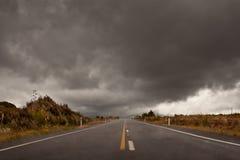 Machen Sie die Straße naß, die in einen bewölkten Himmel des Sturms führt lizenzfreie stockbilder