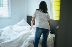 Machen Sie ein Bett, die Frau, die ihr Bett im Raum nach macht, aufwachen stockfoto
