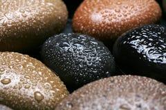 Machen Sie farbigen Steinhintergrund, dunkle Kiesel mit Wassertropfen nass Stockbild