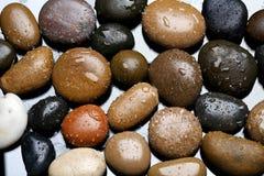 Machen Sie farbigen Steinhintergrund, dunkle Kiesel mit Wassertropfen nass Stockfotografie
