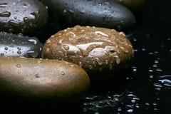 Machen Sie farbigen Steinhintergrund, dunkle Kiesel mit Wassertropfen nass Lizenzfreies Stockbild