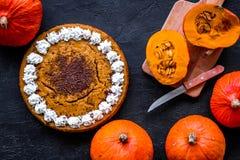 Machen Sie Kürbiskuchen Ganzer Kuchen nahe Kürbisen auf Draufsicht des schwarzen Hintergrundes Lizenzfreie Stockfotografie