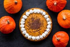 Machen Sie Kürbiskuchen Ganzer Kuchen nahe Kürbisen auf Draufsicht des schwarzen Hintergrundes Lizenzfreie Stockfotos