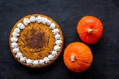 Machen Sie Kürbiskuchen Ganzer Kuchen nahe Kürbisen auf Draufsicht des schwarzen Hintergrundes Stockbild