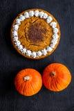 Machen Sie Kürbiskuchen Ganzer Kuchen nahe Kürbisen auf Draufsicht des schwarzen Hintergrundes Stockfotos