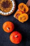 Machen Sie Kürbiskuchen Ganzer Kuchen nahe Kürbisen auf Draufsicht des schwarzen Hintergrundes Lizenzfreie Stockbilder