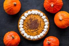 Machen Sie Kürbiskuchen Ganzer Kuchen nahe Kürbisen auf Draufsicht des schwarzen Hintergrundes Stockfoto