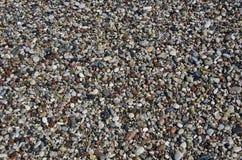 Machen Sie kieseligen Strandsteinhintergrund im Mittelmeerstrand nass Stockfotos