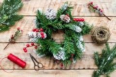 Machen Sie Weihnachtskranz Fichtenzweige, Kegel, Threads, Schnur, sciccors auf Draufsicht des hellen hölzernen Hintergrundes Lizenzfreies Stockfoto