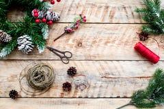 Machen Sie Weihnachtskranz Fichtenzweige, Kegel, Threads, Schnur, sciccors auf Draufsicht des hellen hölzernen Hintergrundes Stockfoto