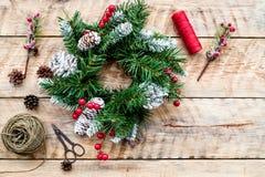 Machen Sie Weihnachtskranz Fichtenzweige, Kegel, Threads, Schnur, sciccors auf Draufsicht des hellen hölzernen Hintergrundes Lizenzfreie Stockfotos