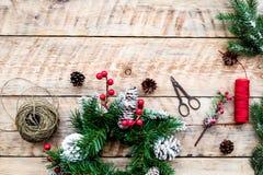 Machen Sie Weihnachtskranz Fichtenzweige, Kegel, Threads, Schnur, sciccors auf Draufsicht des hellen hölzernen Hintergrundes Lizenzfreie Stockfotografie