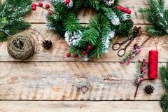 Machen Sie Weihnachtskranz Fichtenzweige, Kegel, Threads, Schnur, sciccors auf Draufsicht des hellen hölzernen Hintergrundes Stockfotografie