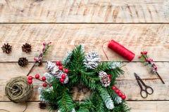 Machen Sie Weihnachtskranz Fichtenzweige, Kegel, Threads, Schnur, sciccors auf Draufsicht des hellen hölzernen Hintergrundes Lizenzfreies Stockbild
