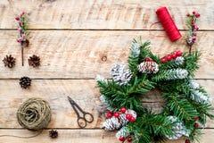 Machen Sie Weihnachtskranz Fichtenzweige, Kegel, Threads, Schnur, sciccors auf Draufsicht des hellen hölzernen Hintergrundes Stockfotos