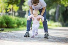 Machen Unterstützungsbabytochter der Mutter und das Helfen sie erste Schritte stockfotos