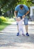 Machen Unterstützungsbabytochter des Vaters und das Helfen sie erste Schritte lizenzfreie stockbilder