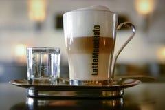 Machiato del Latte servido con agua Foto de archivo