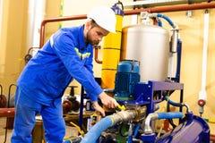 Machinalny inżynier usługuje przemysłowego nafcianego wyposażenie na benzynowej rafinerii obraz royalty free