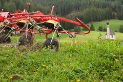 Machinalny narzędzie używać rolnikiem ruszać się siano na łące Fotografia Stock