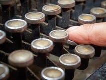 Machine à écrire de dactylographie de vintage de doigt de plan rapproché couverte de poussière images libres de droits