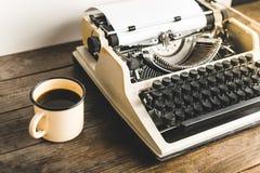 Machine à écrire de vintage et une tasse de café chaud sur un Tableau en bois Jo Images libres de droits