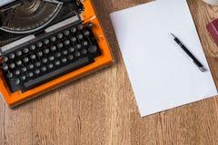 Machine à écrire orange de vintage avec le papier et le stylo Espace de travail d'auteur Images libres de droits