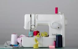 Machine à coudre électrique de ménage et approvisionnements de couture, sur le gris Photo stock
