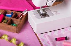 Machine à coudre, accessoires, coupe de tissu sur le bureau Photos stock