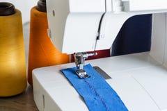 Machine à coudre, aiguille et tissu Images stock