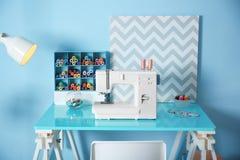 Machine à coudre avec le tissu sur la table Photos stock