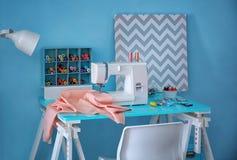 Machine à coudre avec le tissu sur la table Images stock