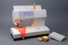 Machine à coudre avec les amorçages et le tissu Photos stock