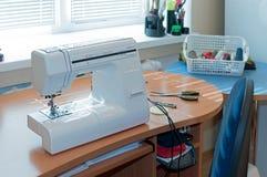 Machine à coudre blanche, chaise bleue, bobines de fil dans le panier près de la fenêtre photo libre de droits