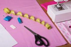 Machine à coudre, centimètre, craie et ciseaux sur le tissu rose Photos libres de droits