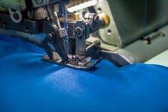 Machine à coudre d'overlock professionnel avec le tissu bleu Photo libre de droits