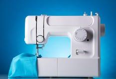 Machine à coudre dans le travail avec le tissu, sur le bleu Image libre de droits