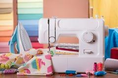 Machine à coudre dans le travail et des accessoires, sur le fond des échantillons de tissu Photos stock