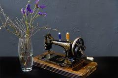Machine à coudre de cru un vase avec les fleurs bleues photographie stock