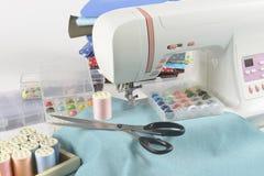Machine à coudre et petits pains de fil, ciseaux, tissu et a colorés Photos libres de droits