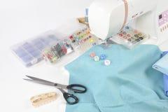 Machine à coudre et petits pains de fil, ciseaux, tissu et a colorés Photo stock